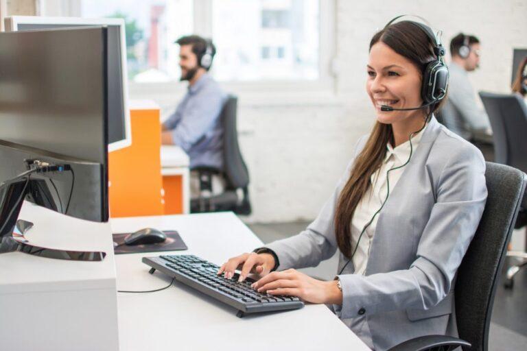 Hymyilevä asiakaspalvelija tietokoneella