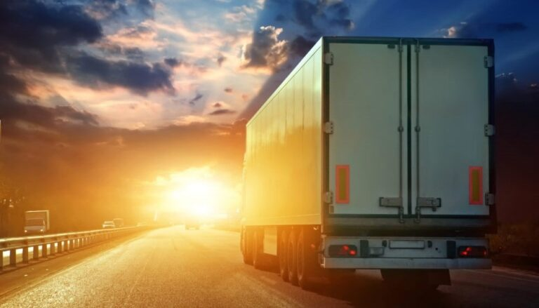 Kuorma-auta ajaa auringonlaskussa