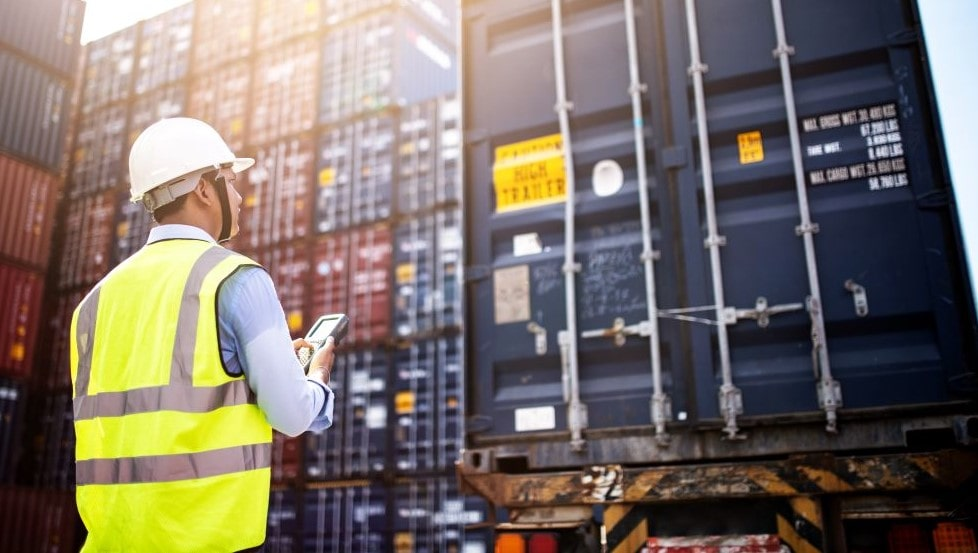 Työntekijä tarkistaa maantiekuljetus konttia
