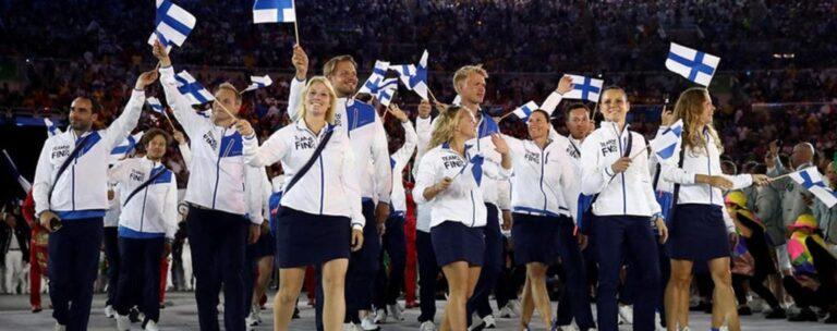 Suomen olympiamaajoukkue heiluttaa Suomenlippuja
